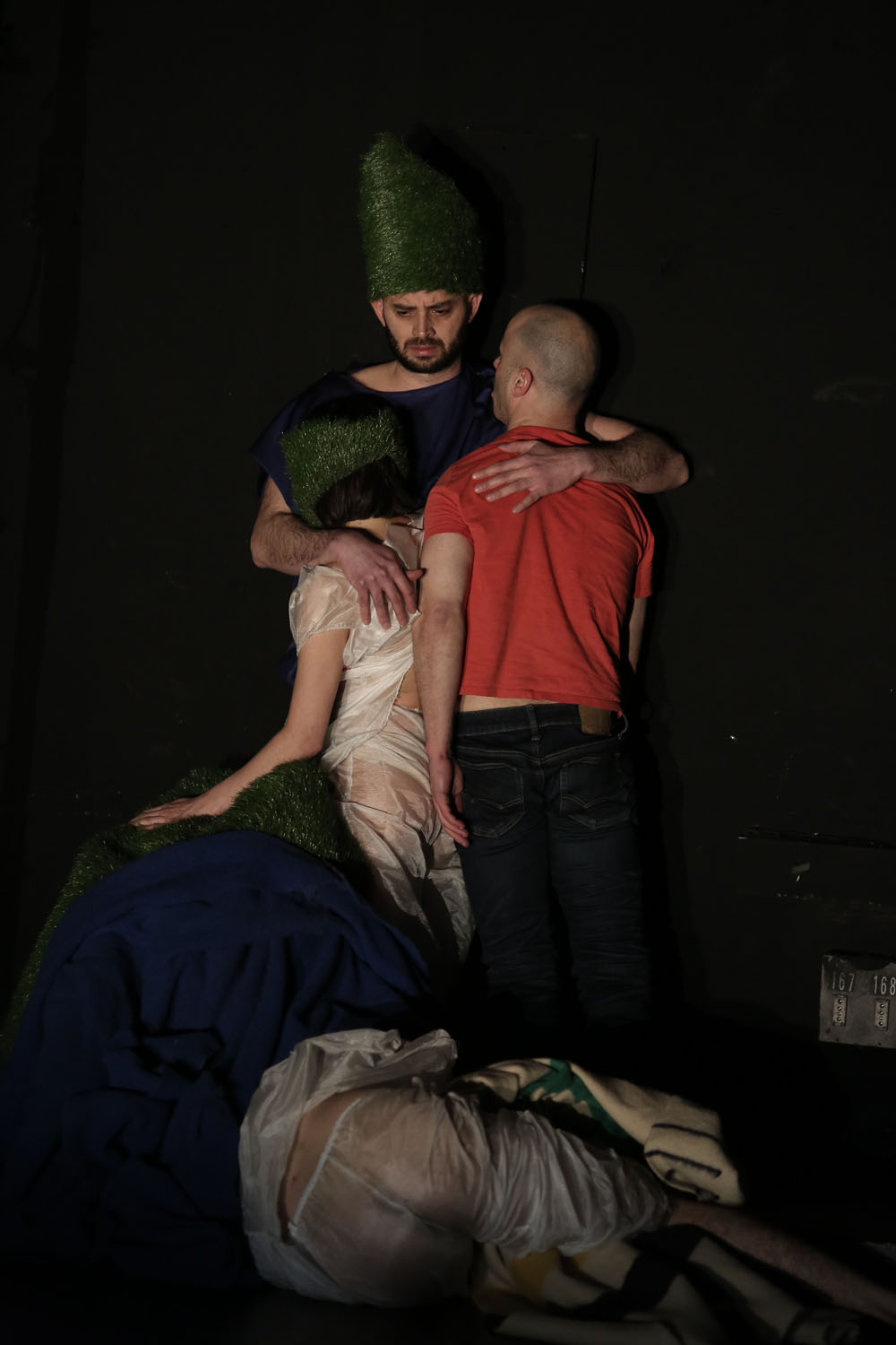 Christopher hugs performers Vanessa and Butch. Below, a mountain of fabrics where the performer Arantxa hides and another performer named Mar rests on the ground sideways. Vanessa and Christopher wear masks and hats made from plastic grass.
