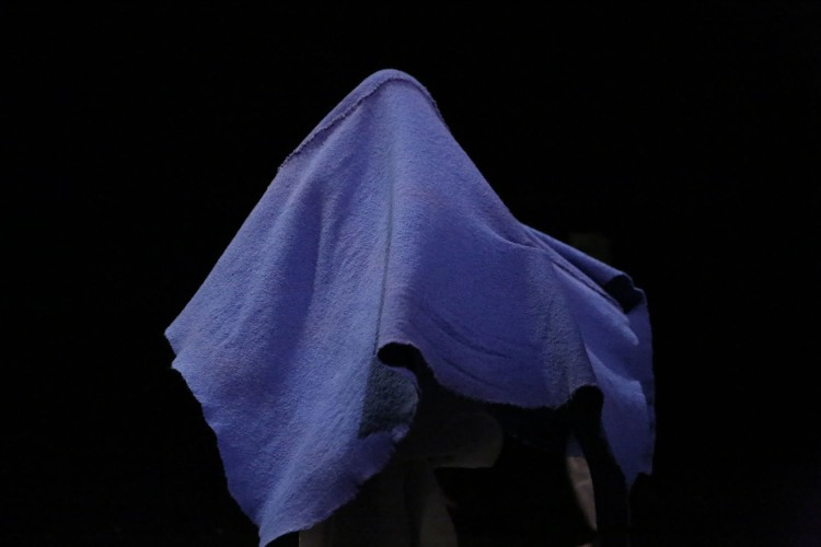A performer named Mar is covered with a sky blue cotton blanket making a ghost shape