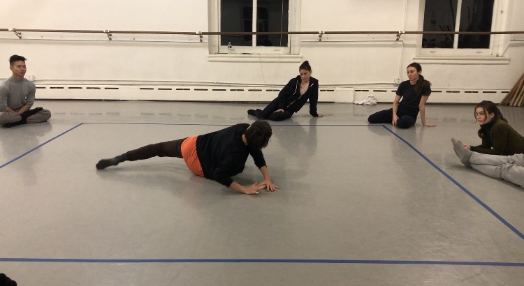 Image Description: Battery Dance Company members Mira Cook, Sarah Housepian, Vivake Khamsingsavath, Bethany Mitchell, Razvan Stoian, Hussein Smko and Jillian Linkowski explore movement and description to their movement inside a square marked on the floor with blue masking tape.