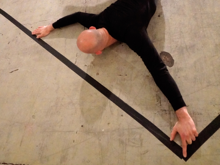 Christopher is face down dressed in black and marking a black line on the floor with tape.