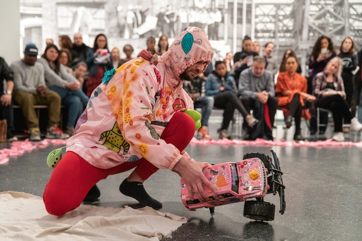 Christopher is dressed in a pink hoodie decorated with personal objects and red leggings. He holds a pink three-wheeled remote control car and is surrounded by a line of pink cloth and several people in the background.