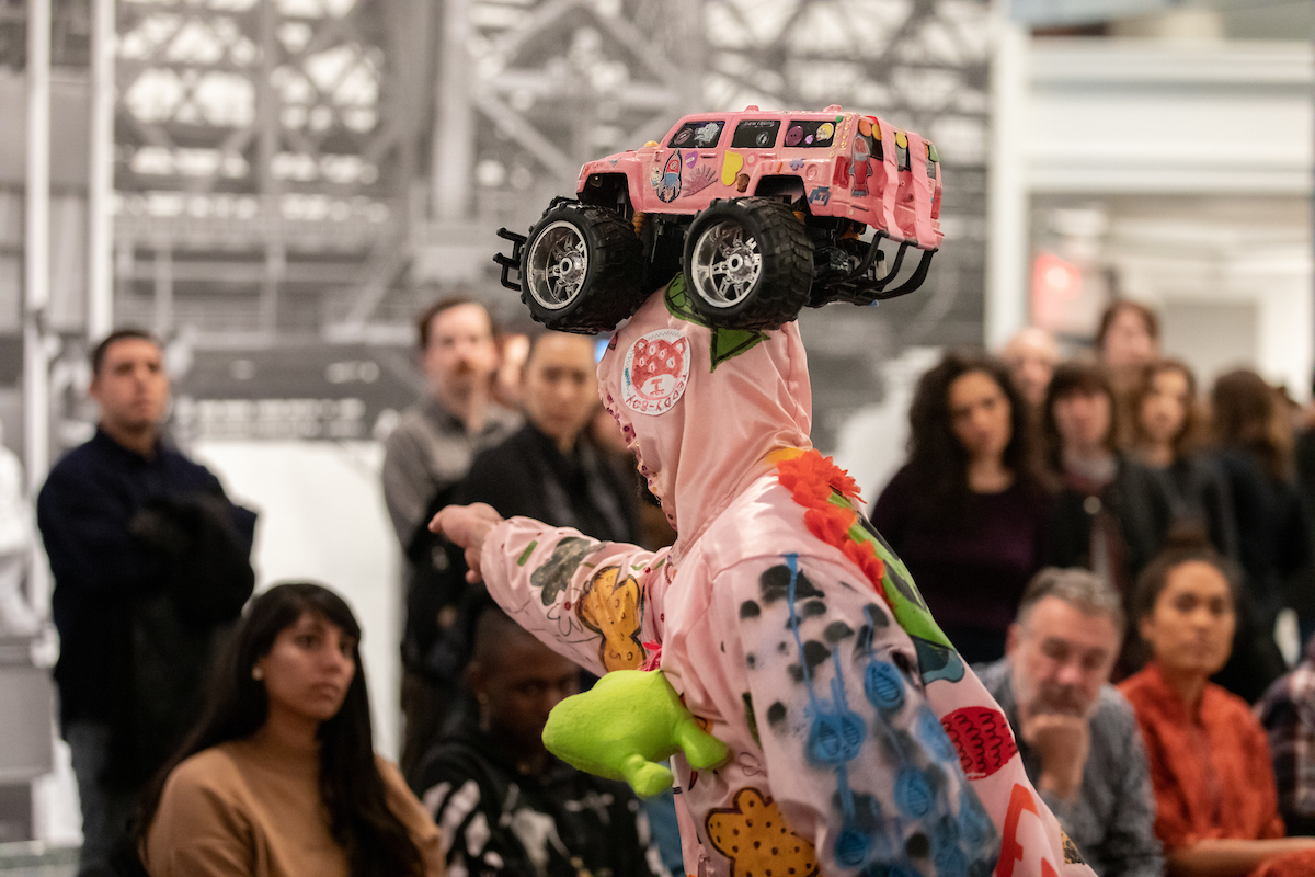 Christopher wears a pink hoodie decorated with various personal objects. He holds a three-wheeled remote-controlled pink car as a hat on his head. In the background we see several people from the audience.
