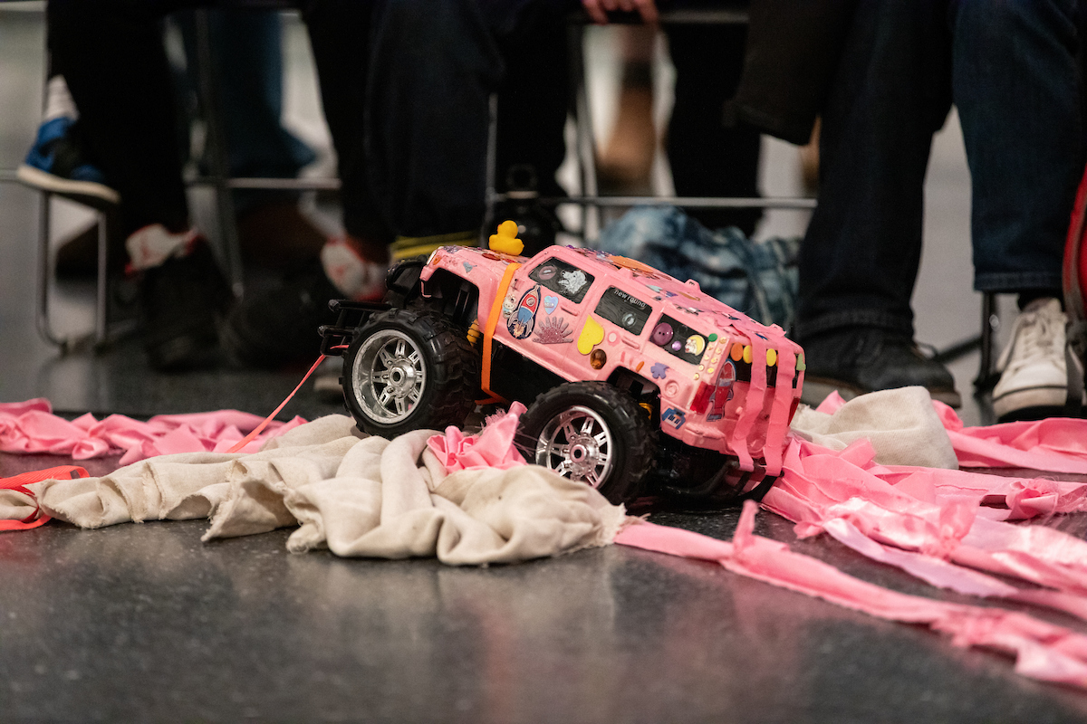 There is a pink remote control car decorated with various stickers and toys surrounded by pink ribbon. In the background we see the feet of the audience.
