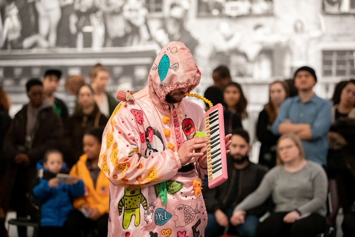 Christopher is dressed in a pink hoodie decorated with various personal objects. He holds a melody in his hands and blows a straw to produce sound. In the background we see several people from the audience.