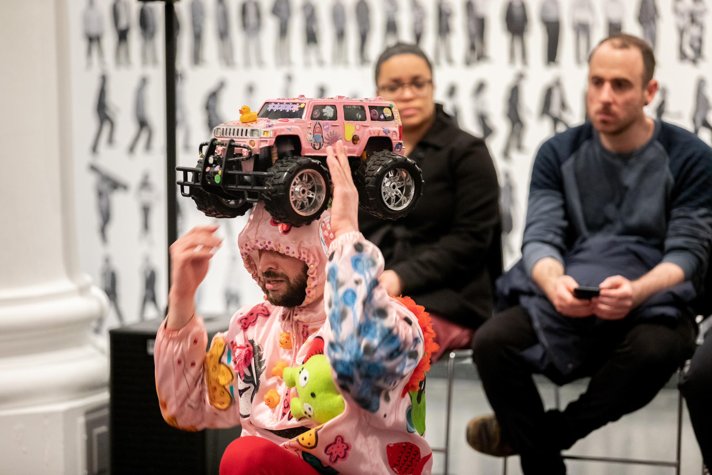 I am wearing the pink remote control car on my head as a crown. I've become a mythological creature. In the background the audience admires my kingdom with bewilderment.
