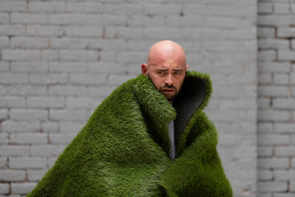 Christopher hugs a coat made of grass and conjures up the image of a raging mountain. His facial expression is intense and his forehead is sweating.