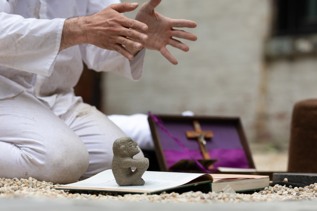Christopher's hands gesture over a Sukia figure, an indigenous 800-year-old shamanic sculpture made of volcanic rock. In the background a Catholic crucifix with a purple background. Pain and colonization inhabit the body.